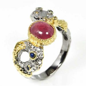 טבעת עבודת יד כסף 925 ציפוי זהב ורודיום שחור בשיבוץ אבן מרכזית רובי (מוזמביק) ואבני ספיר מידה : 11 הטבעת: 32 קרט